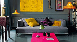 A grey living room with yellow wall art and accessories