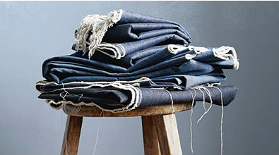 A pile of denim jeans on a wooden stool