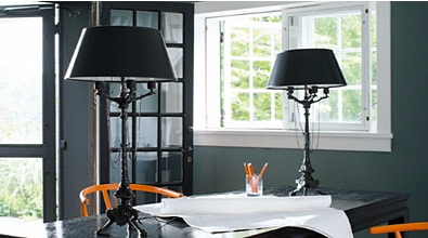 Black lampshades on a black table, in a dark blue-ish grey living spade