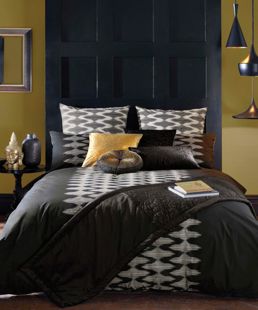Black and white bedding with gold cushions, in front of a tall blue headboard and yellow mustard walls