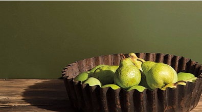 Dark olive green kitchen, with bowl of pears on a wooden counter