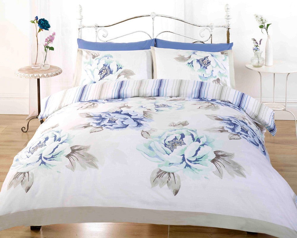 White bedding with blue flowers and beige leaves, on a metal bed frame