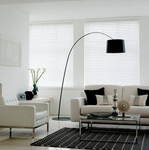 White and cream living room with cream sofas and white venetian blinds at two windows