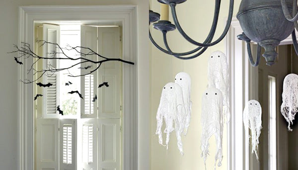 Small white fabric ghosts hanging from the ceiling, with dangling black bats too