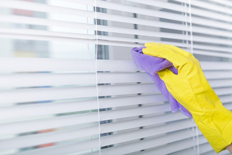 White venetian blinds being cleaned with a purple cloth