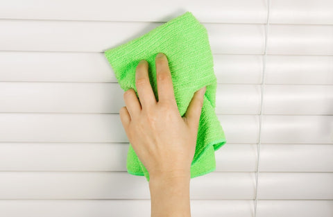 Cleaning white venetian blinds with a green dusting cloth