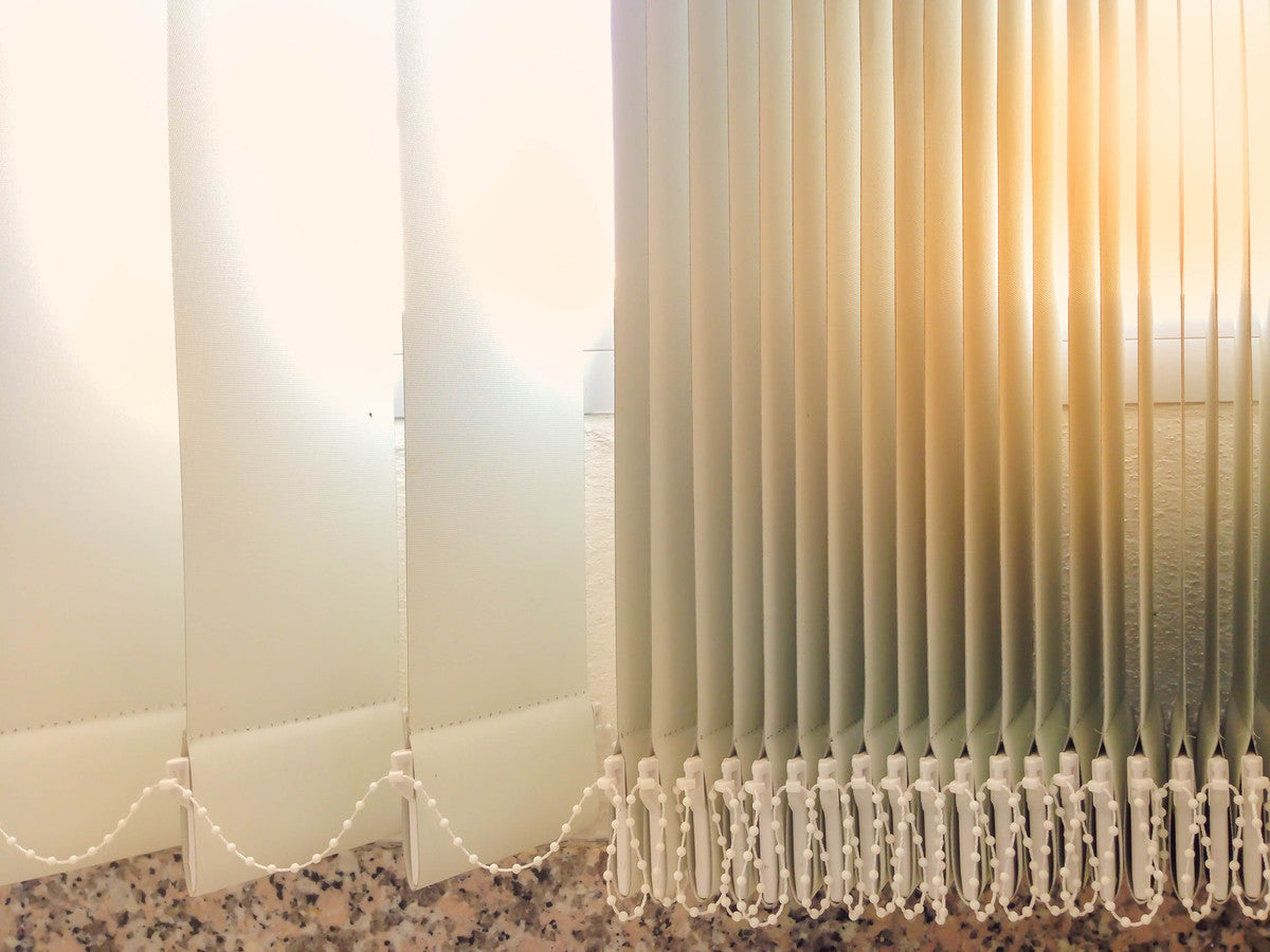 Bunched vertical blinds with bright sunlight seaping through the slats