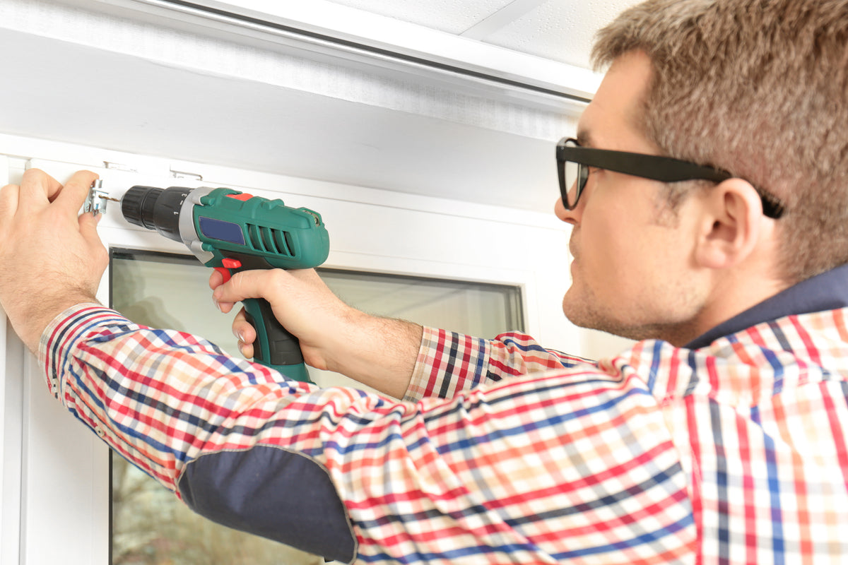 A man using an electric drill to screw a bracket to a white PVC window frame