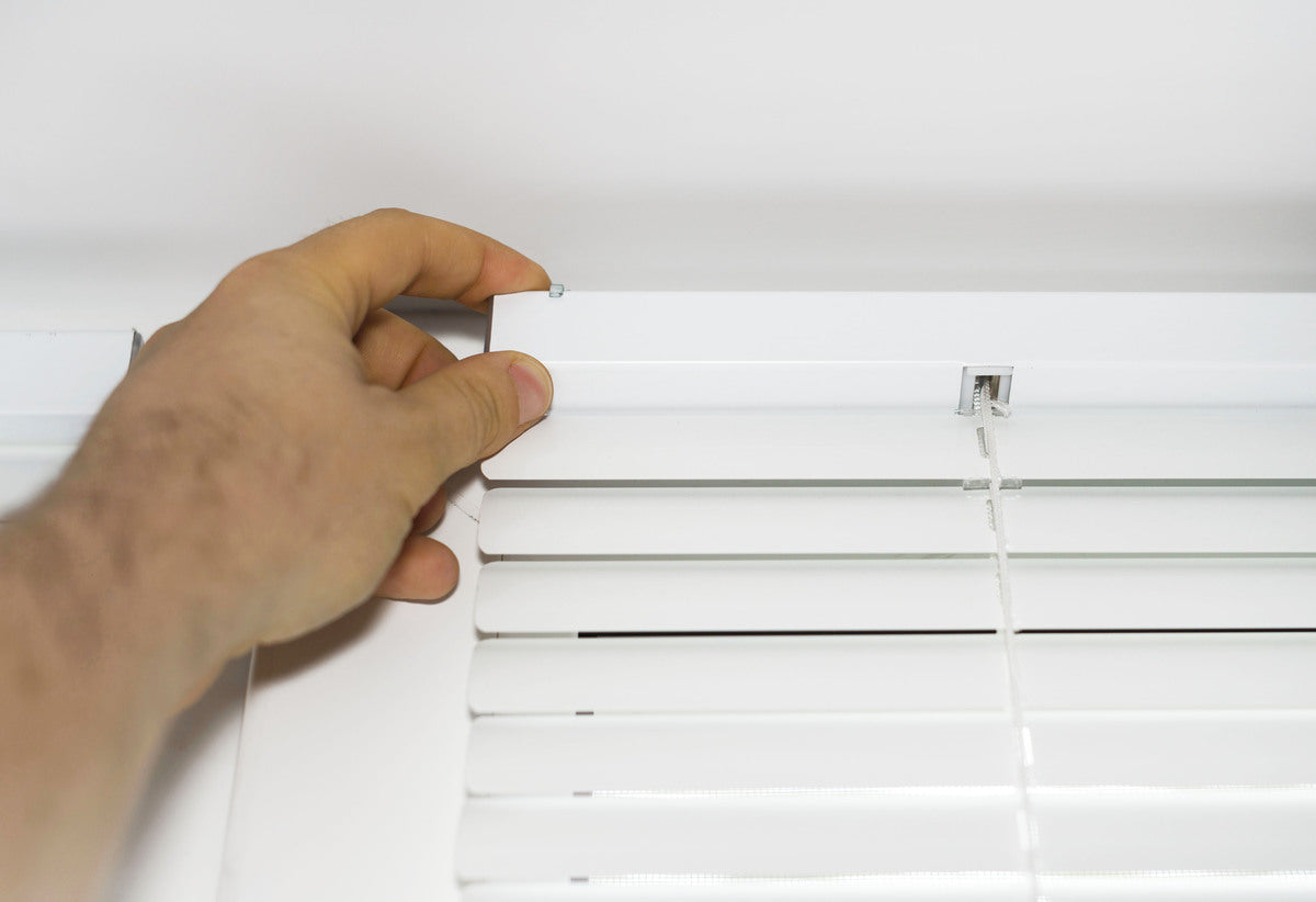 A hand attaching a white venetian blind header rail into its support bracket
