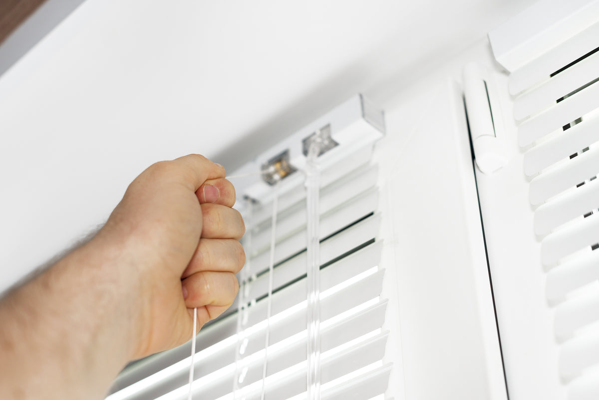 A hand pulling the opening cord on a white venetian blind