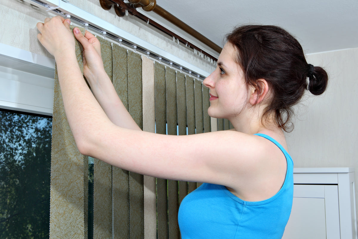 A woman attaching vertical blind slats to a header rail