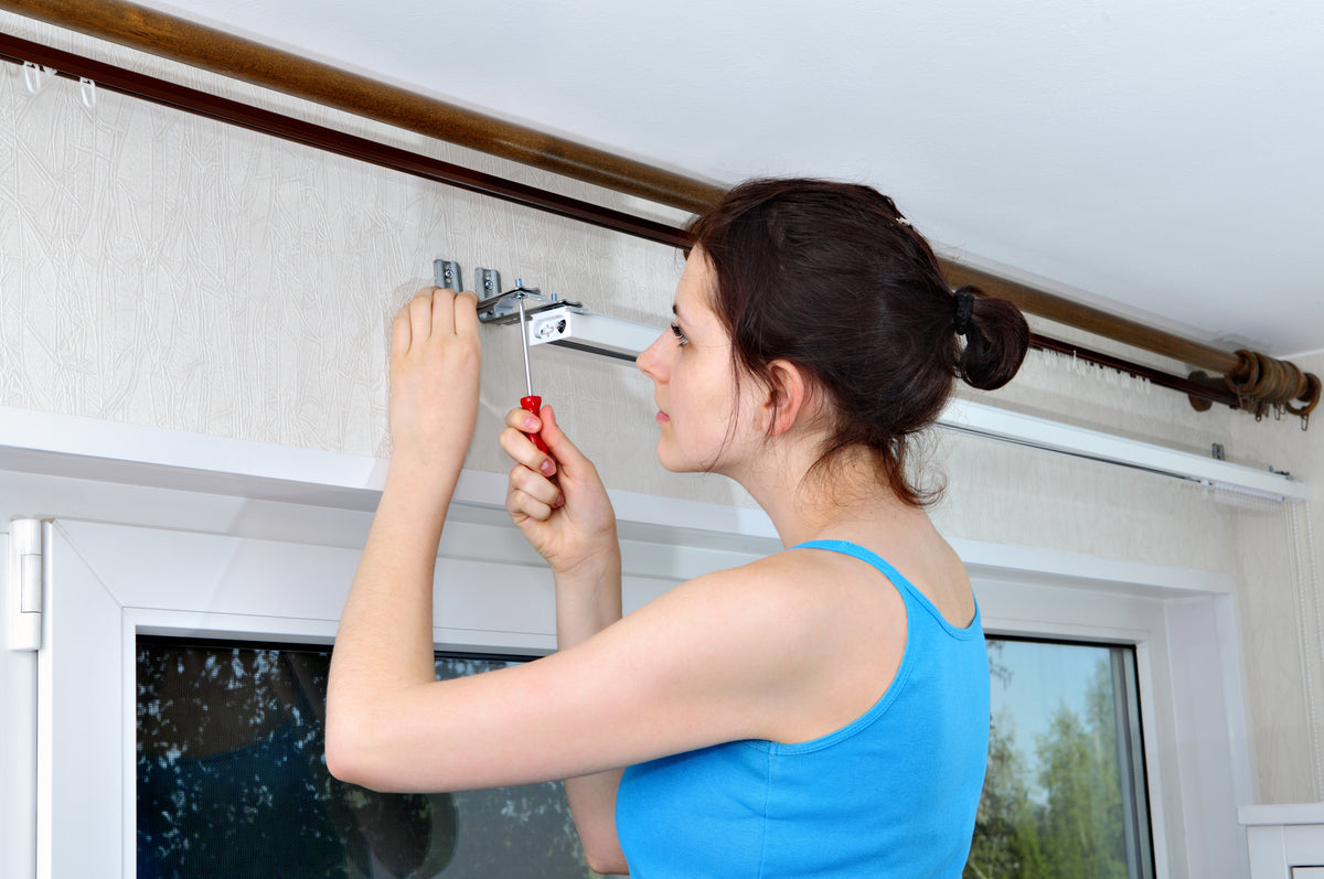 A woman using a screwdriver to secure a vertical blind header rail onto a support bracket