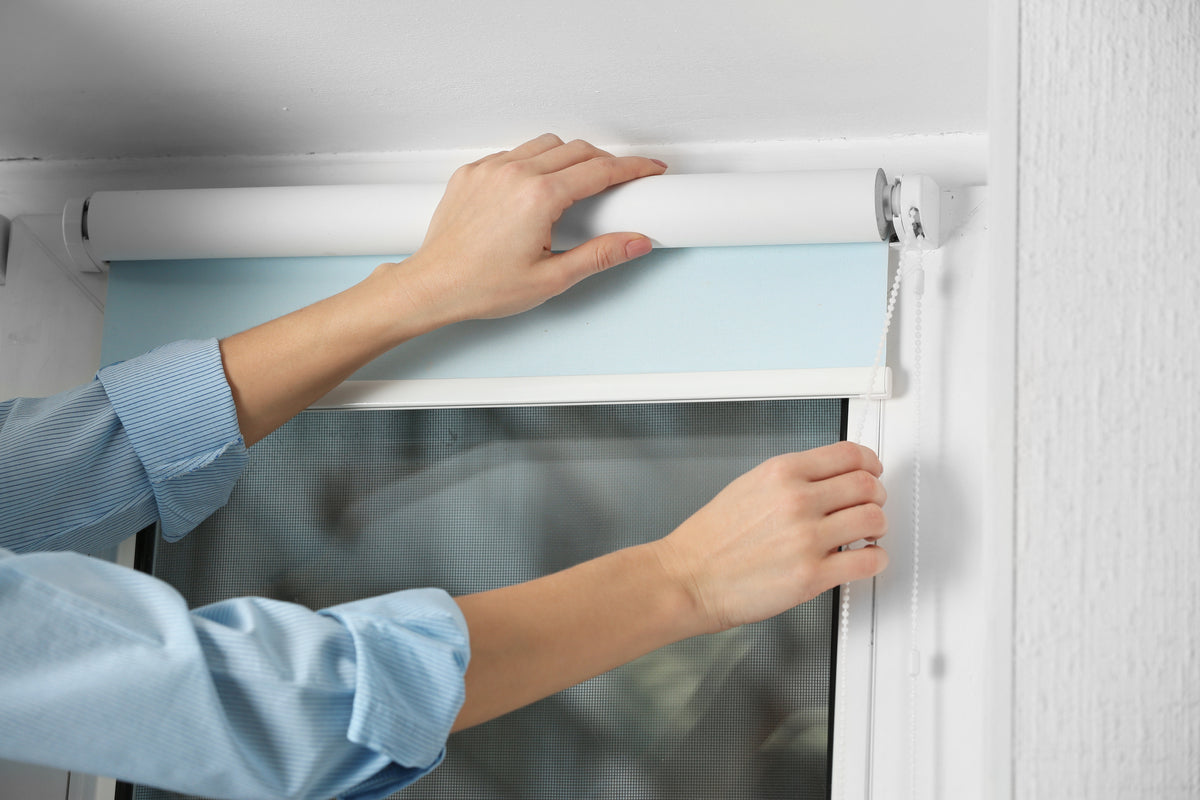 A pair of hands securing a light blue roller blind in place and testing the opening cord