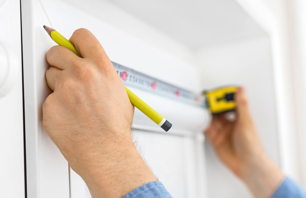 A tape measure stretched across the width of a window, measuring up for a roller blind