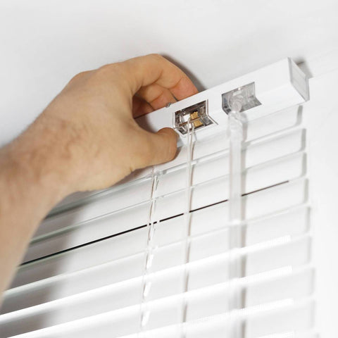 A hand adjusting the top of a white venetian blind