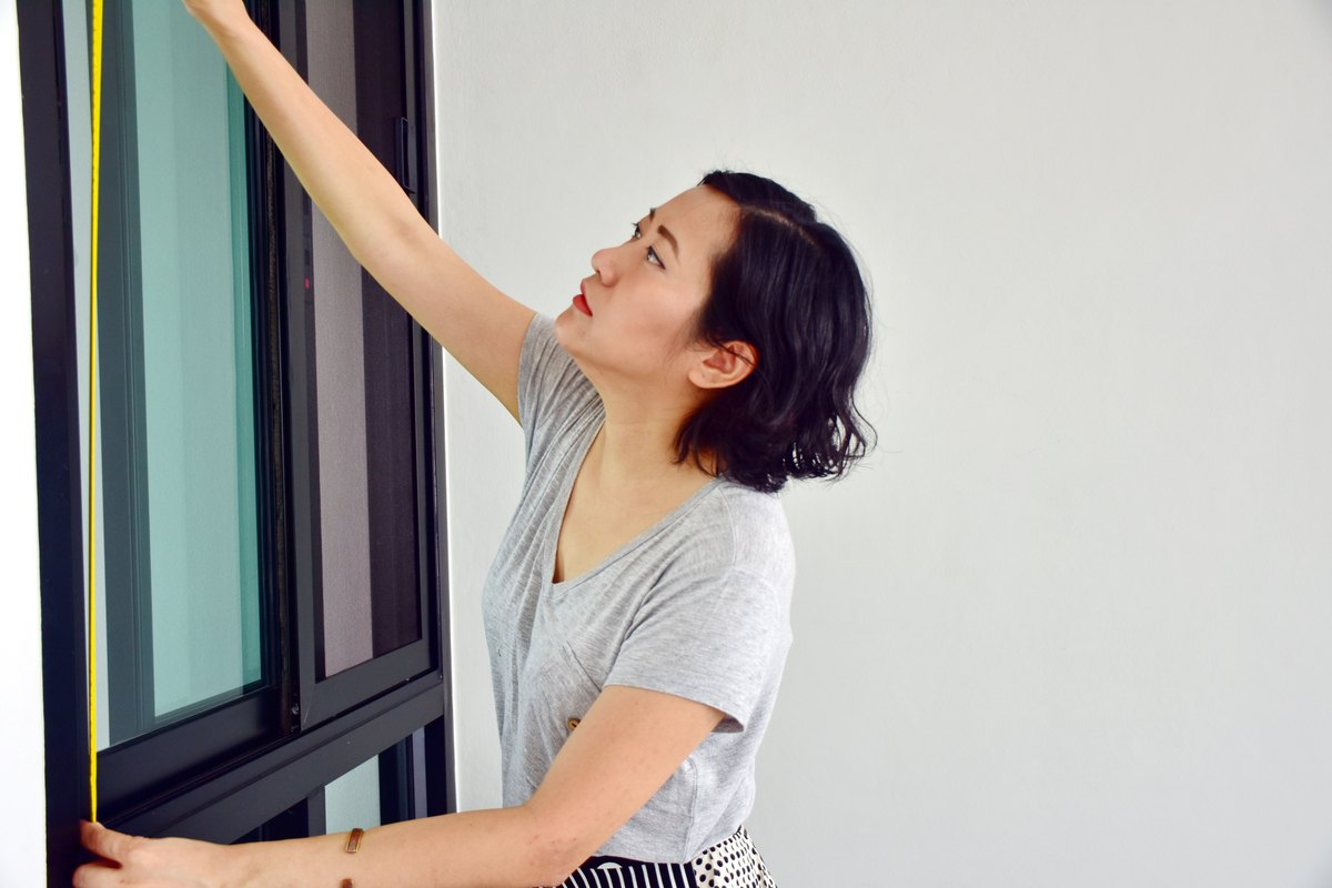 Woman measuring a window for new curtains