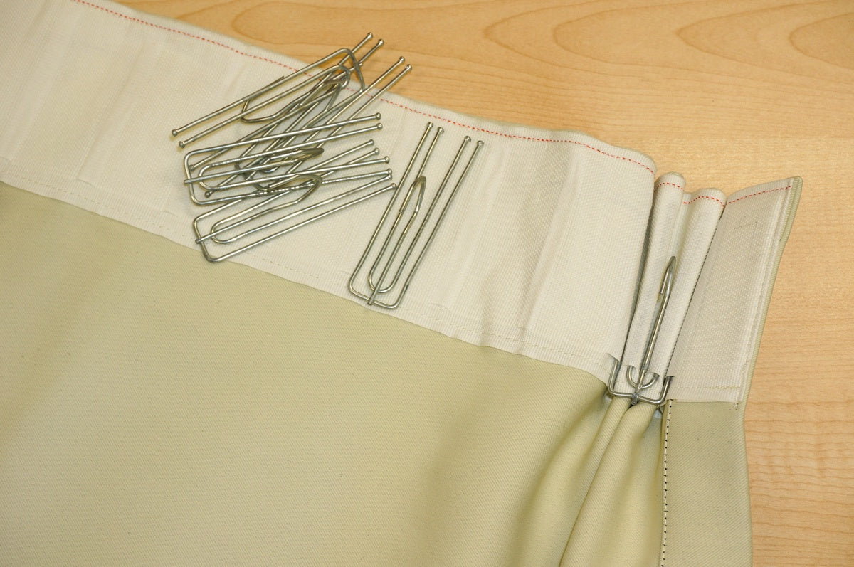 Curtain pin hooks attached to pencil pleat curtains