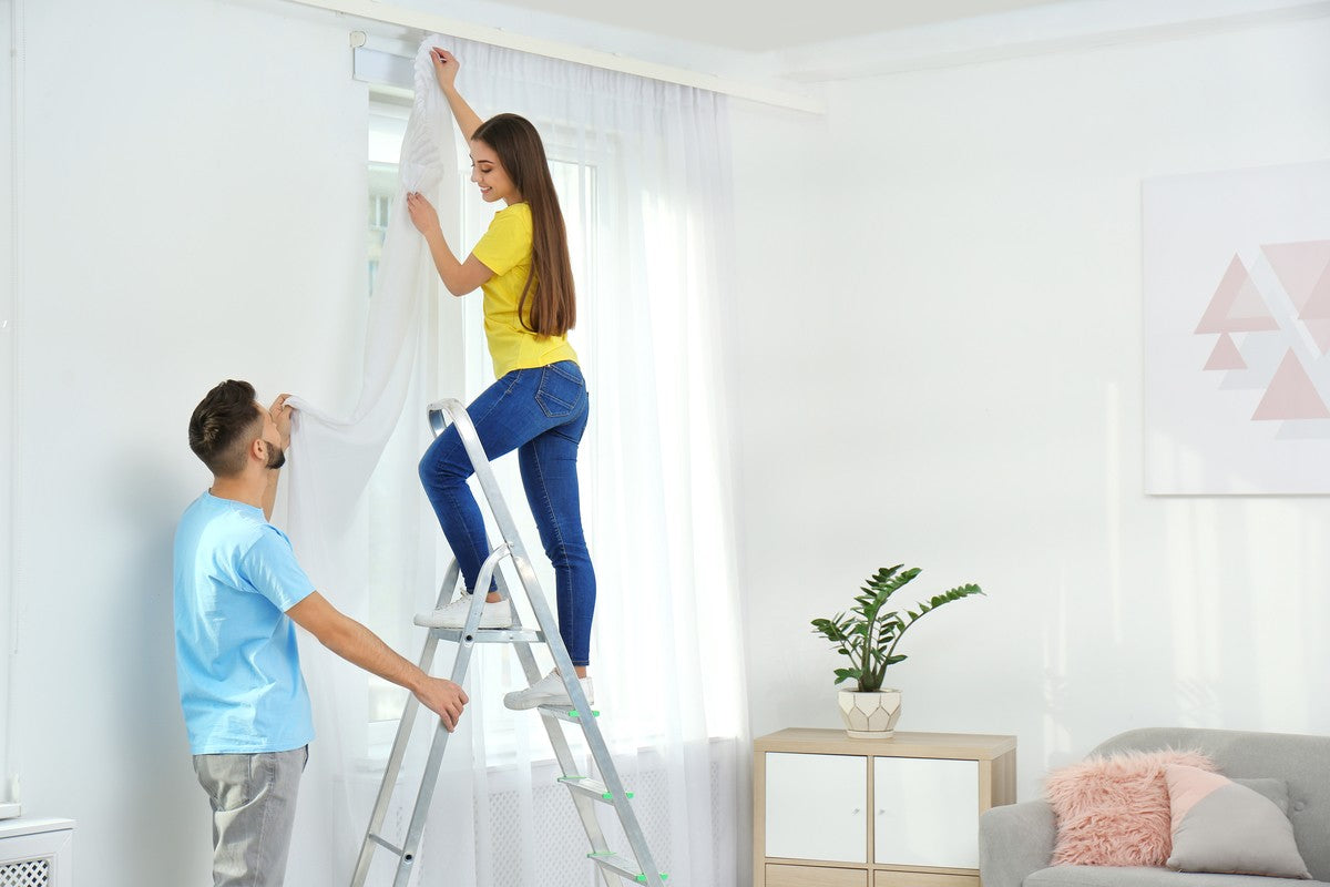 A couple with the man holding a ladder and the woman at the top hanging curtains