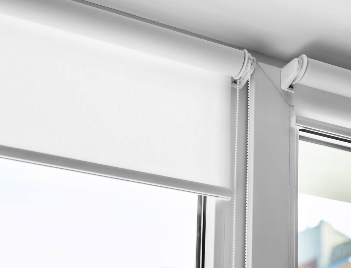 A white roller blinds set within a window