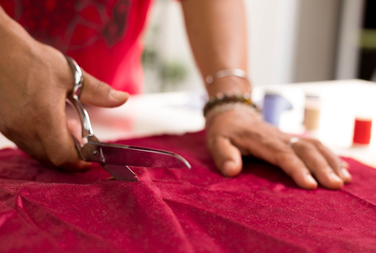 Scissors being used to cut through red fabric