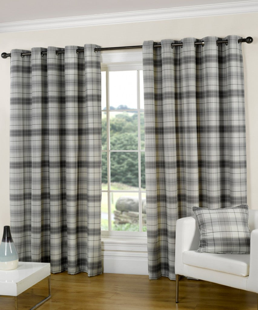 Grey striped and checked eyelet curtains at a window