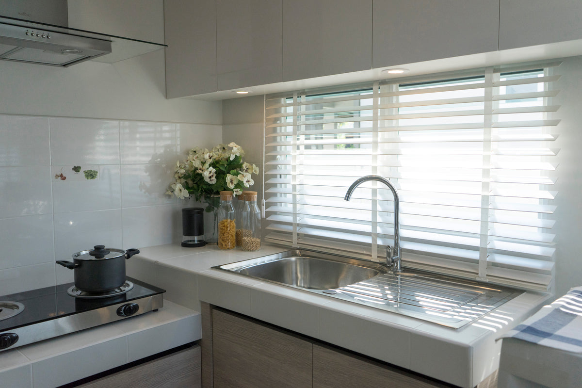 White venetian blinds at a kitchen window, above a shiny metal sink