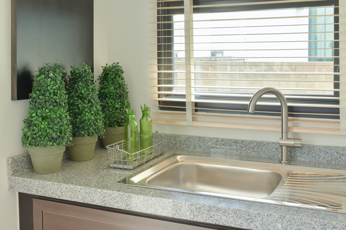 Beige venetian blind at a kitchen window, with three planters on the counter top