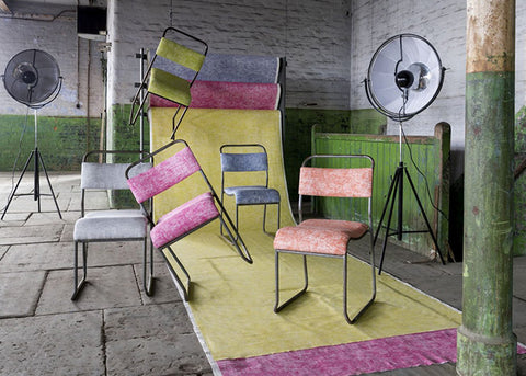 Metal chairs with different coloured backs arranged on yellow fabric as part of a photoshoot