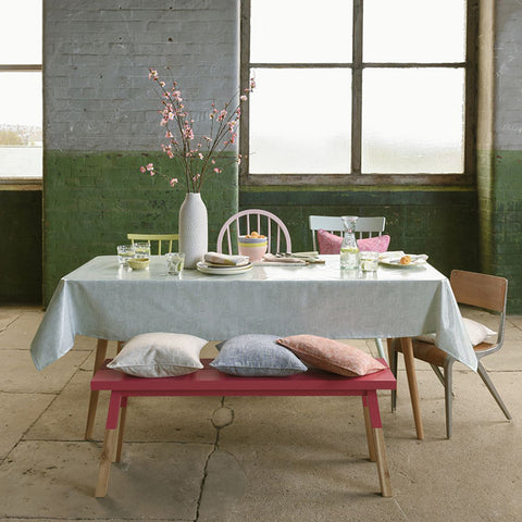 Urban living space with grey and green painted bricks and dining table with PVC tablecloth