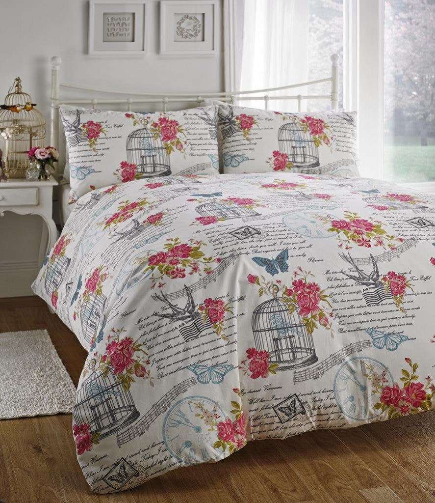 White bedding with script writing, pink flowers, grey bird design and blue butterflies