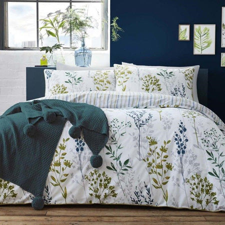 Dark blue bedroom with white bedding adorned with dark green and blue floral pattern