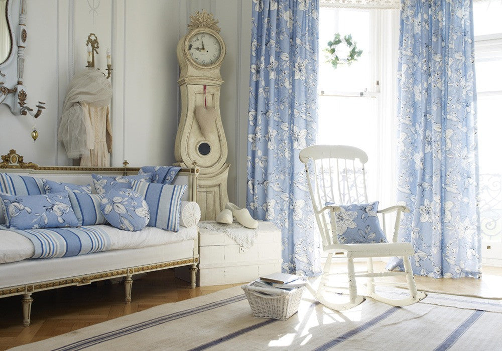 Blue and white floral curtains in a bay window, matching cushions on a white wooden frame sofa and antique cream grandfather clock