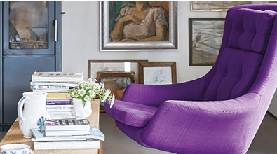 Purple comfy swivel chair at small wooden table with books on top of it