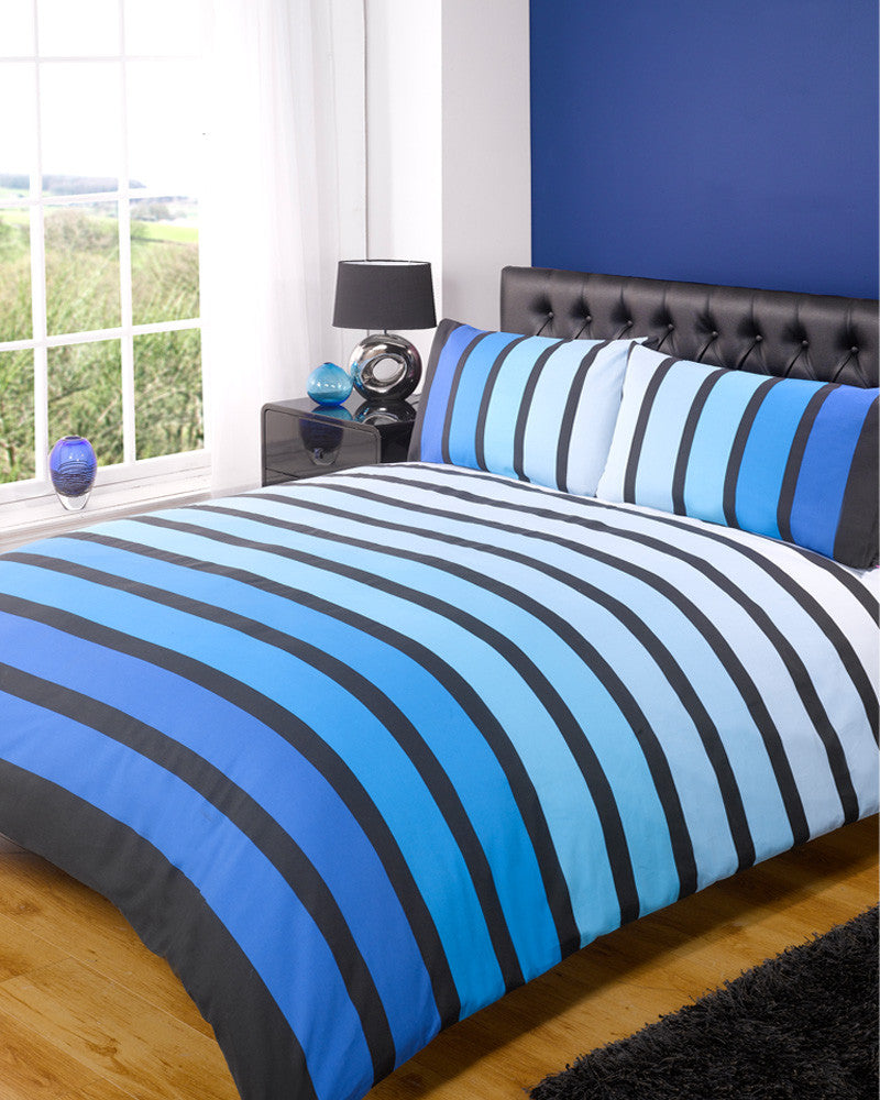 Striped bedding with dark blue stripes that gradually get lighter until they are final white, each blue strip separated by a bold black line
