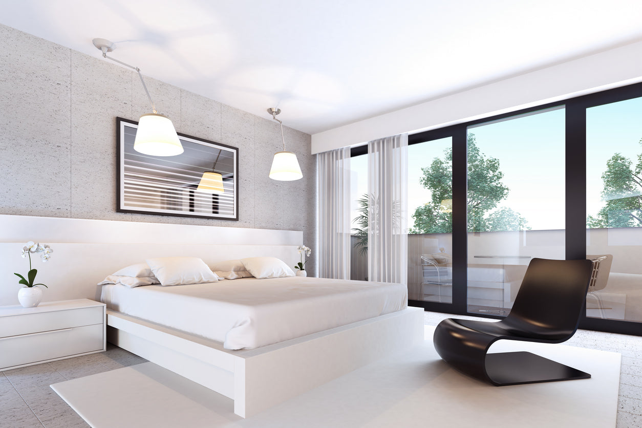 Modern white bedroom with black funky chair at the bottom of the bed