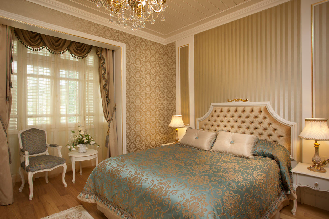 Traditional bedroom with gold patterned walls and green and gold damask bedding