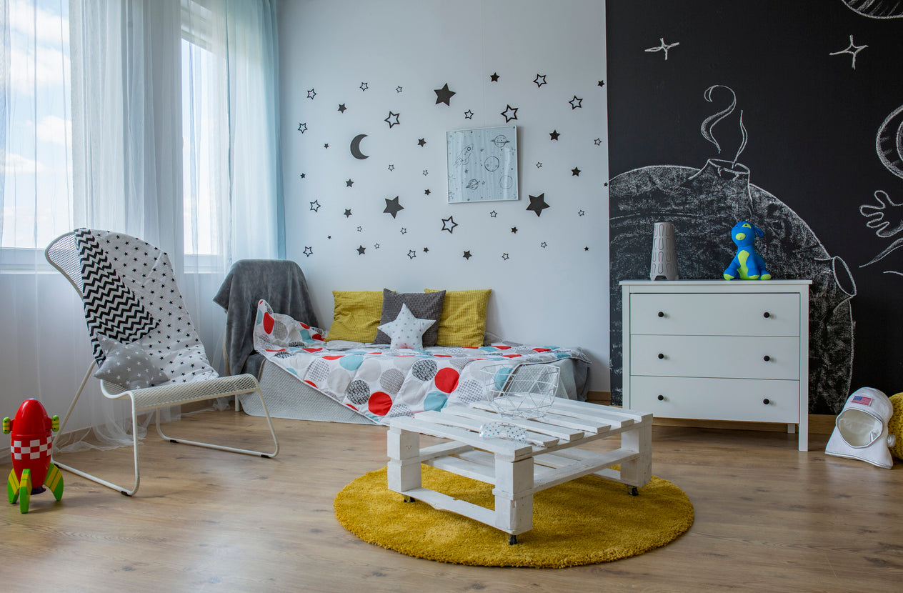 Funky Space Themed Childs Room With Black Chalkboard Wall To Spark Creativity