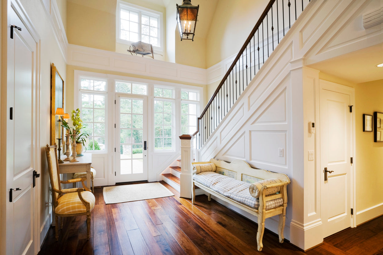 Large cream hall and front door with dark wood floors and chairs