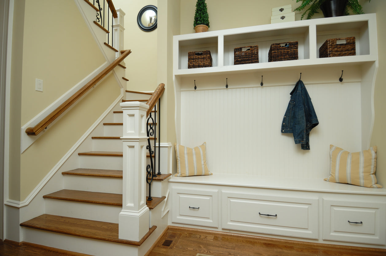 Cream hall and stairs with wood stain steps, and coat rack and shoe bench
