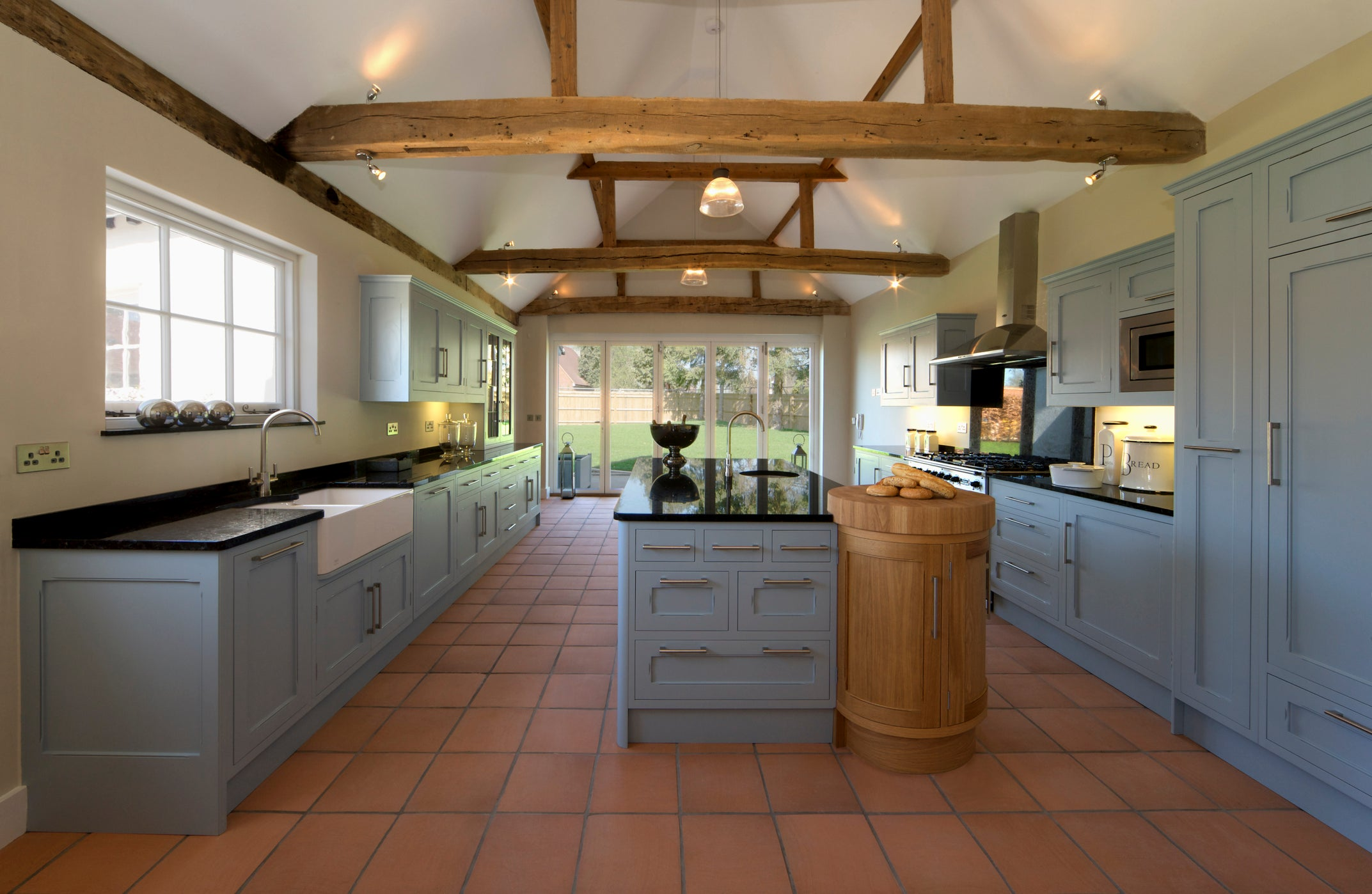 Grey kitchen units, cream walls and traditional ceramic floor tiles