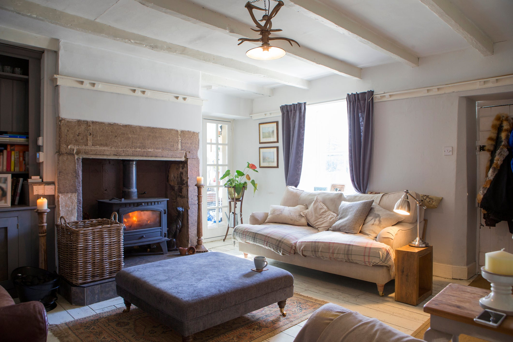 Country cottage living room, cosy chairs and roaring log fire