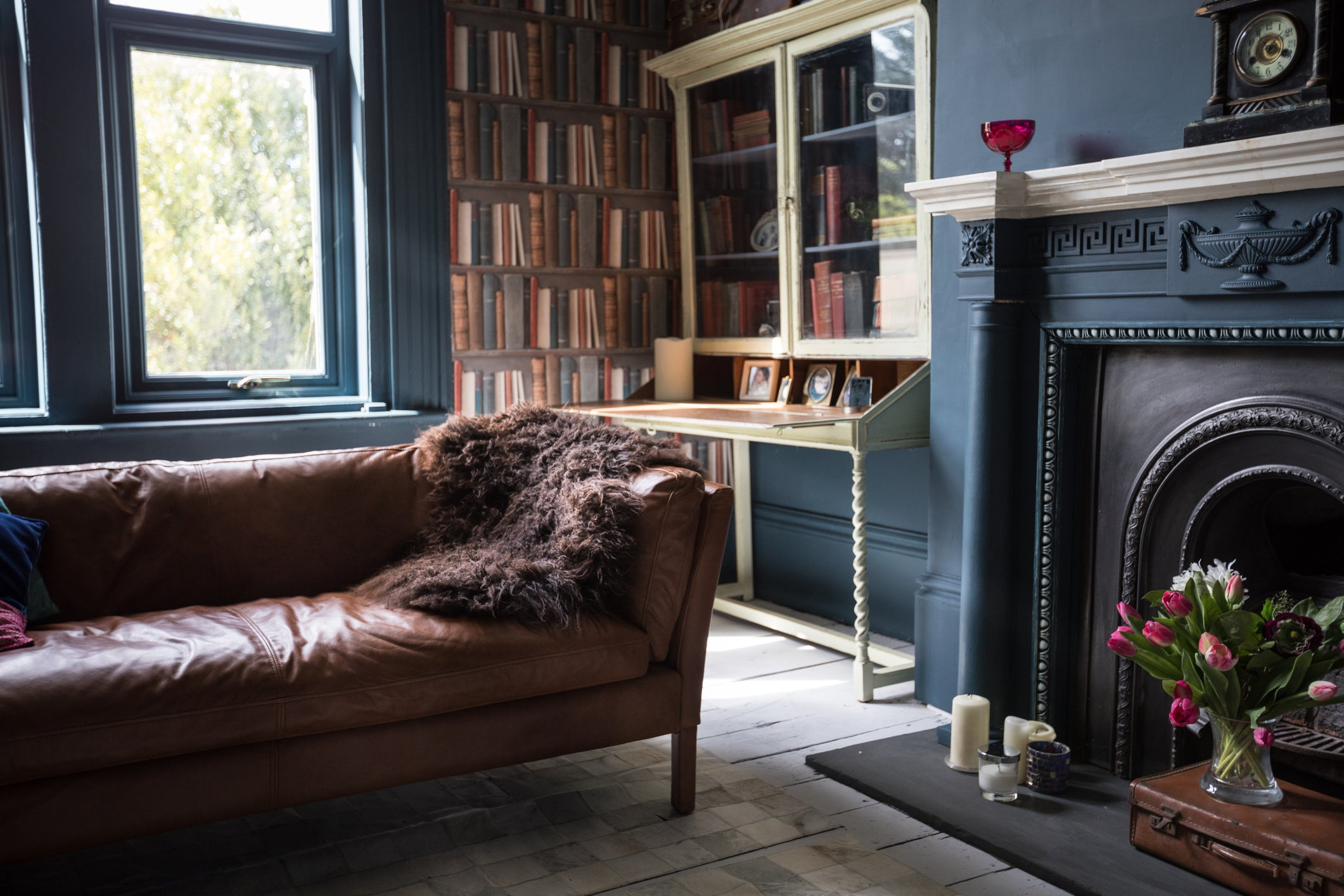 Black living room, with black fireplace and black window frames, then a dark brown leather sofa and bookshelf in the corner