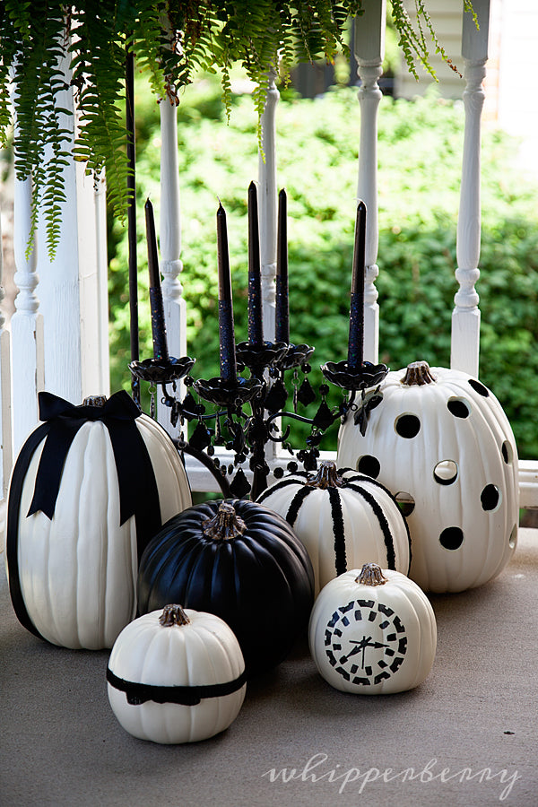 Black and white pumpkins and a black candelabra