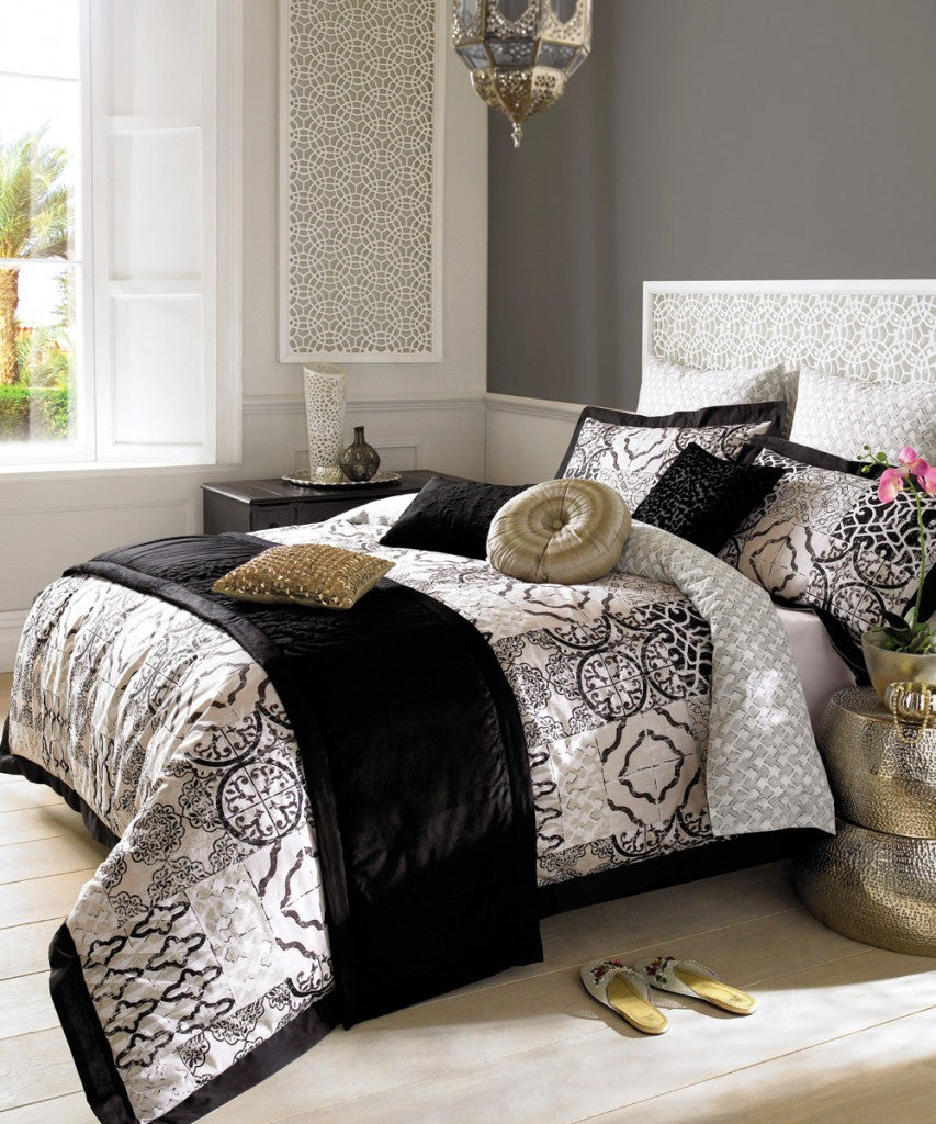 Black and white silky fabric bedding, with two gold cushions