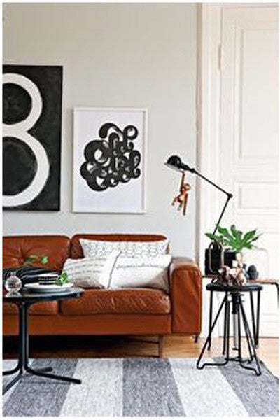 White living room with dark brown leather sofa and black and white wall graphics