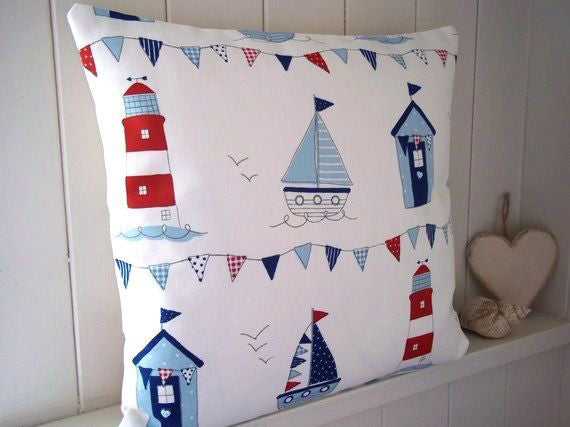 Beach huts, lighthouses and boats on a cream cushion