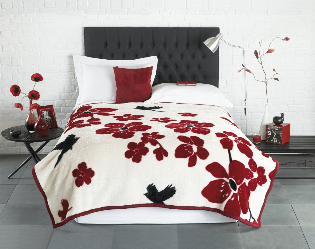 White bedding with a thick red and white throw, with red flowers and black bird design
