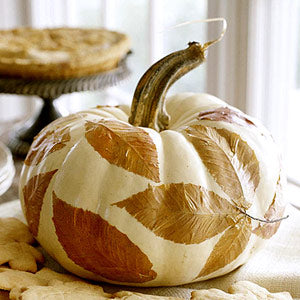 A pumpkin painted white covered in autumnal leaves