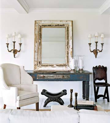 Cream living space with cream arm chair and a mirror in a rustic white and gold frame