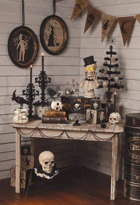 Corner of a room with white wooden panels on the walls and a white table containing lots of skulls and black Halloween ornaments